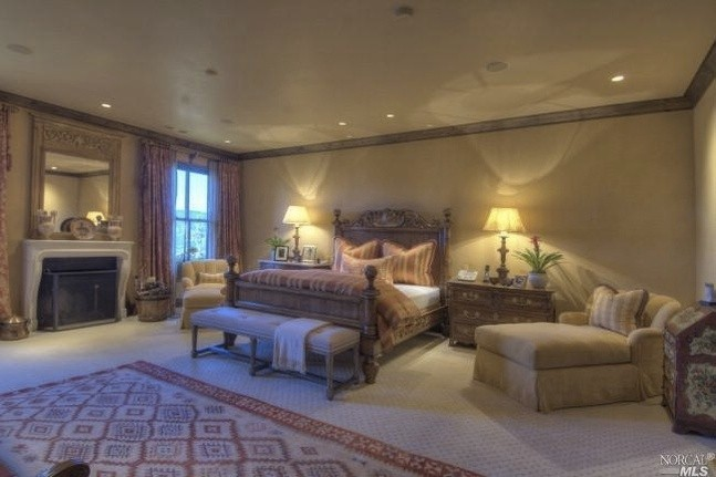 The master bedroom, although large, does not feel uncomfortably so because of the wall color choice, the stained wood trim, light  patterned carpeting, with another colorful one on top that picks up the color in the bedding and curtains. The fireplace is stone and the huge mirror over the mantel is a perfect addition.