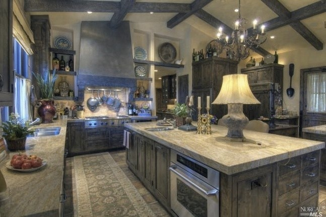 I really like the stone counter choice, and the cabinetry is so right for this kitchen. No white kitchen here! Details that make this room so beautiful.....the lamp on the island, the hood over the stove cooktop with drawers below, the niches to the left and right of the hood, and the beams.