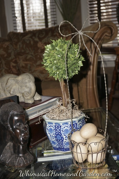 A small wire basket  that often holds a small potted plant, now holds brown paper eggs, and sits on the library table near the arrangement above. The little wire basket was a find for $1 last year at the Thrift store and I have done lots of fun things with it.
