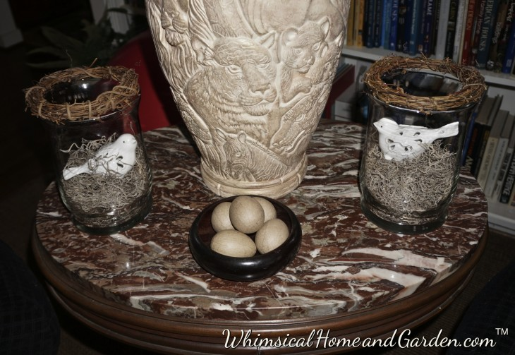 In this arrangement, a bit more rustic and earthy, I took $4 glass containers and put a couple of birds I usually place in outdoor containers for interest, inside on top of some spanish moss, and topped with a twig mini-wreath. I took one of my wood salad bowls and put a few brown paper eggs inside.....done!