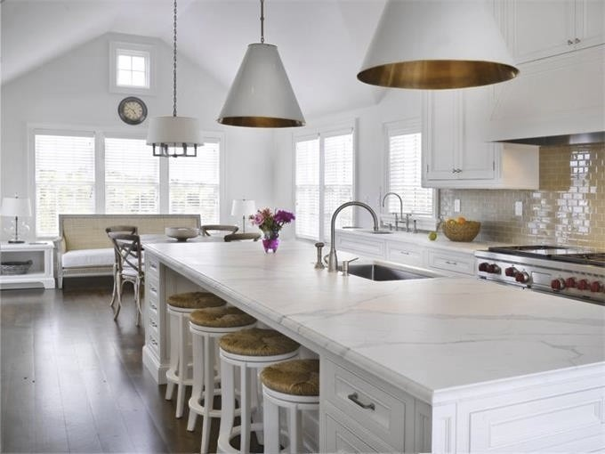 Bright white kitchen, perfect for the kind of light you get here, with subtle color in backsplash, lining of the island light fixtures and repeated again in the stool coverings. The wood floors set a warm tone for the room.
