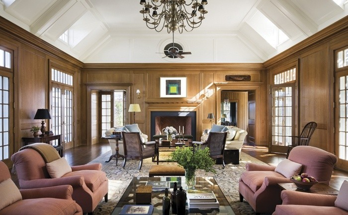 Full view of the living room. Although a large room, light flows in from multiple sets of french doors, while the dormers flood the room with even more. The two seating arrangements allow for both a large group of people or an individual to feel comfortable despite the rooms size. The vaulted ceiling is in wonderful proportion to the wall height. A touch of Modern art above the fireplace mantel add an unexpected pop of color.
