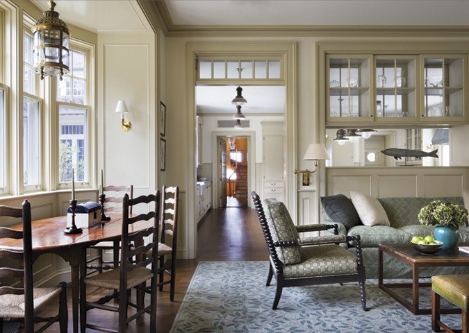 The site lines and proportions are beautiful and perfect, inviting you to want to see what is beyond this room. Minimal nautical touches such as the lantern over the table and the fish over the sofa. Colors muted, complimenting the gorgeous wood furniture, which looks pretty comfortable......