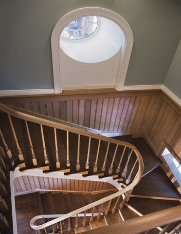 The staircase is another subtle nod to a nautical style, with a staircase that reminds one of the stairs in a lighthouse. The deeply set window like a porthole. Notice the window at floor level......The darker wood stair treads set off the wood paneled walls.The curves of the stair rails are beautiful.