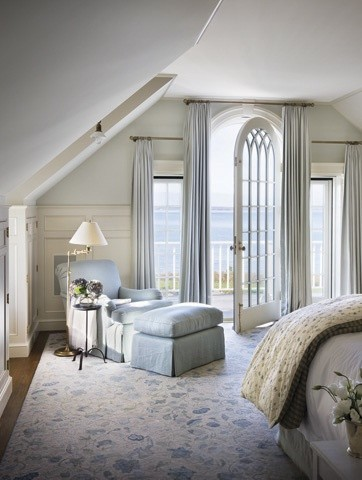 The shape of the door and the ceilings add architectural interest without competing with the stunning views of the ocean right outside the doors. Soft blues, creams and comfortable furnishings - it would be difficult to want to get up and move from this bedroom!