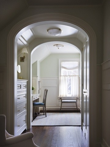 The woodworking of this barrel vaulted entranceway is beautiful. The built in chest and closet are again, an understated nod to what one would find on a ship. The small small sconce over the dresser repeats throughout the house, e.g. in the dining room there are 4 that are visible. The dark stained floors set off the white and muted paint colors.