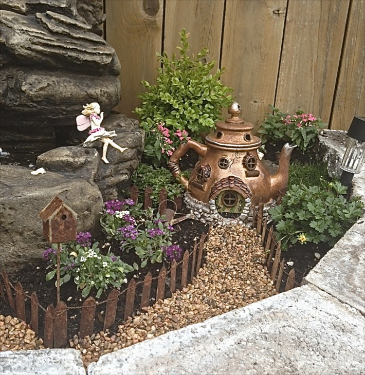 This Fairy Garden Started With A Teapot House. The Little Fairy Sits Atop  Rocks While Surveying Her Garden, All Fenced In. There Are Many Plants That  Are ...