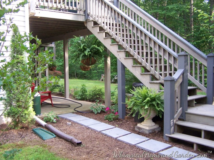 Here are the stairs leading up to the deck with the rails and post caps now dark gray. The house of the side to the left has a second story board and batten  cedar bump out stained a darker gray, so it ties it to the shutters in the front and this side.